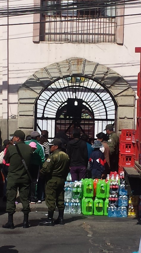 The delivery of drinks into San Pedro. Visitors also crowd around the front gate.